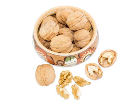 isolation: Walnuts in a ceramic bowl with floral ornaments and beside whole walnut, walnut splited in half and several nut kernels on a white background. Isolation.