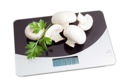 wholes: Several uncooked wholes and halfs of champignon mushroom and one leaf of fresh parsley on digital kitchen scale on a light background. Isolation