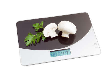calibrated: Home digital kitchen scale with a two champignon mushrooms and branch of parsley on working surface on light background. Isolation