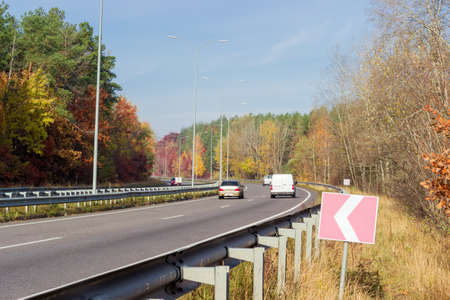 guardrails: Fragment of the motorway with asphalt road surface and road surface marking, lampposts, traffic barriers and forest on both sides autumn morning Stock Photo
