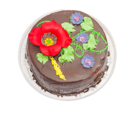 glazing: Round sponge cake, covered with chocolate glazing on top tameing floral ornament. On a light background
