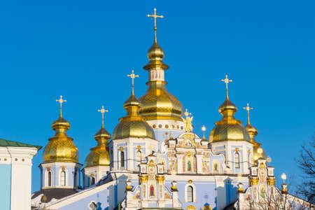 setting  sun: Domes and crosses of St. Michaels Golden-Domed Monastery in the setting sun against the blue sky. Kiev, Ukraine