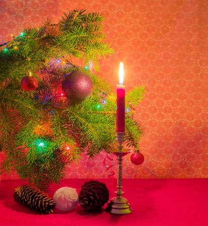 christmastide: Branch of a Christmas trees, decorated with Christmas ornament and lights, fir and pine cones and candle in a candlestick in the light of candle on a red background