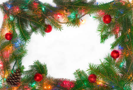 christmas tree ornament: Fir branches, several Christmas ornaments and Christmas mini lights, laid out on the perimeter, as a frame with empty center part on a light background