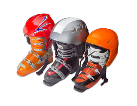 buckles: Three modern alpine ski boots different sizes and colors with four buckles and protective ski helmets on a light background Stock Photo