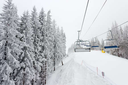 chairlift: Chairlift and ski piste among the spruce forest at ski resort in cloudy weather