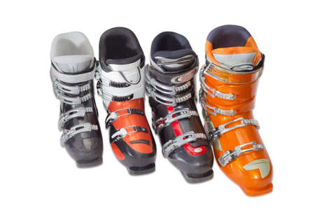 buckles: Four modern alpine ski boots various sizes and colors with four buckles on a light background