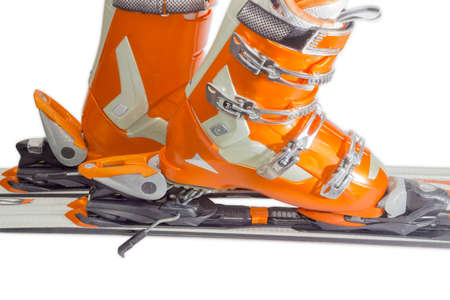 Orange alpine ski boots with four buckles in ski binding. One shoe is completely fastened to the ski, a second just put in binding. 版權商用圖片
