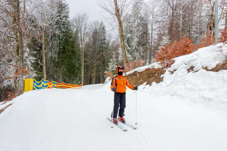 Young skier on start of a piste among the spruce and beech forest Stock Photo