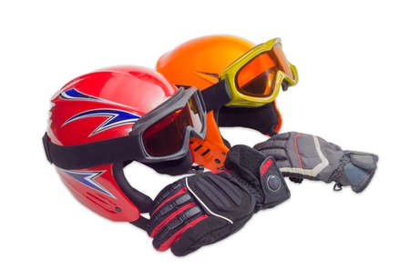 safeness: One red and one orange protective ski helmets with ski goggles and ski glove on a light background