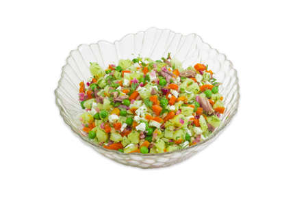 Salad of sliced boiled vegetables, eggs, meat in a glass salad bowl on a light background