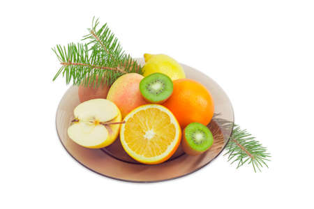 Whole apple, lemon, orange, several kiwifruits and halves of a kiwifruits, apple and orange on dark glass dish and fir branches on a light background