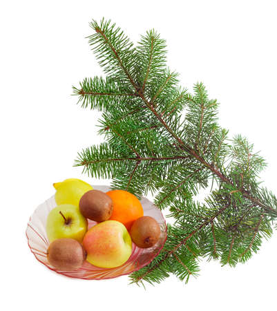 Pink glass dish with several apples, lemon, orange and kiwifruits under fir branch on a light background