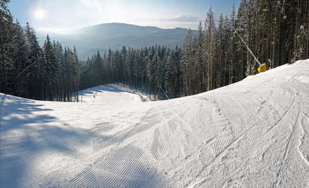 Ski piste with snowmaking surrounded by spruce forest on the background of distant mountain ranges in sunny day