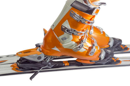 safeness: Orange alpine ski boots with four buckles in ski binding. One shoe is completely fastened to the ski, a second just put in binding. Stock Photo