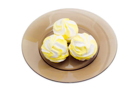 Yellow zefir - soft confectionery, manufactured in countries of the former Soviet Union and similar to marshmallow on a dark glass dish Stock Photo