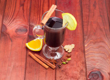 orange peel clove: Mulled wine in glass mug with slice of lemon and mulling spices for cooking a mulled wine on dark red wooden surface