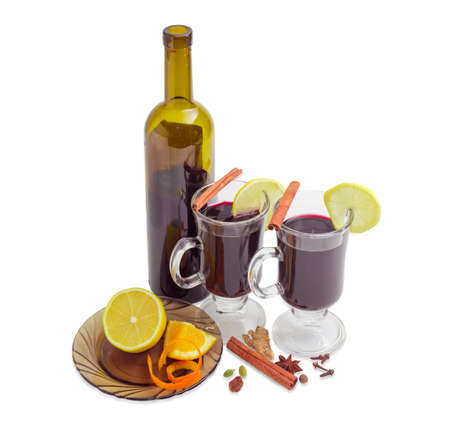 Mulled wine in two glass mugs with slices of lemon, bottle of wine and mulling spices for cooking of a mulled wine on a light background