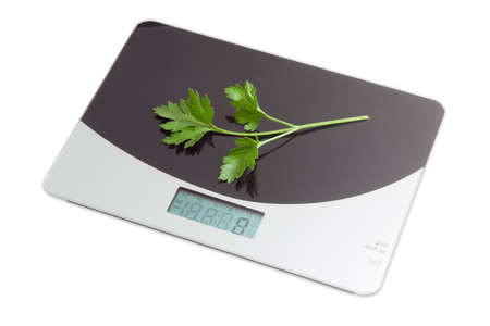 calibrated: Home digital kitchen scale with a branch of parsley on working surface on light background. Isolation