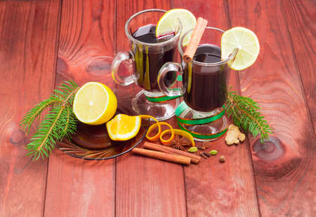 orange peel clove: Mulled wine in two glass mug with slice of lemon, mulling spices for cooking a mulled wine and fir branches on dark red wooden surface Stock Photo