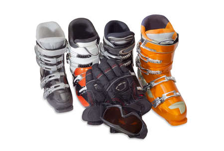 ski goggles: Several modern alpine ski boots various sizes and colors, ski goggles and ski glove on a light background