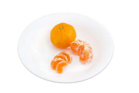 sectioned: One whole and peeled halved and sectioned fresh ripe mandarin orange on a white dish on a light background Stock Photo