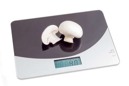 calibrated: Household digital kitchen scale with one whole and one half of a mushroom on working surface on light background
