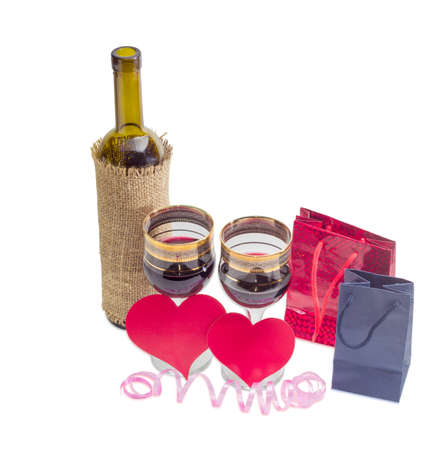 small paper: Two wine glasses with red wine and bottle of wine, two hearts made of red paper and two small paper bags on a light background