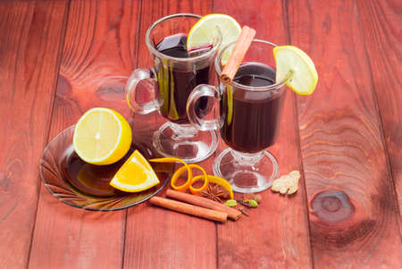 orange peel clove: Mulled wine in two glass mugs with slices of lemon and mulling spices for cooking of a mulled wine on dark red wooden surface