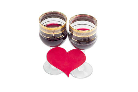 glass ornament: Two wine glasses with red wine and heart made of red paper on a light background