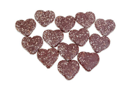 Several cookies in the shape of a heart glazed with chocolate and grated coconut on a light background Stock Photo