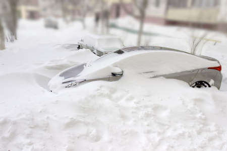 snowdrifts: Snowdrifts blocks a light gray car covered with snow during a snowstorm