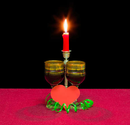 Two wine glasses with red wine, heart made of red paper and burning candle in a candlestick on a table with a red tablecloth on a dark background