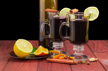Mulled wine in two glass mugs with slices of lemon, bottle of wine and mulling spices for cooking of a mulled wine on dark red wooden surface  against a dark background
