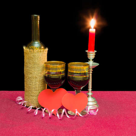 wine glasses: Two wine glasses with red wine, bottle of wine, two hearts made of red paper and burning candle in a candlestick on a table with a red tablecloth on a dark background