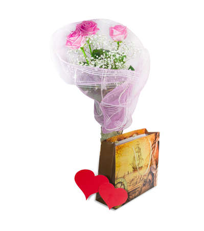 Bouquet of pink roses, souvenir paper bag and two hearts made of red paper on a light background