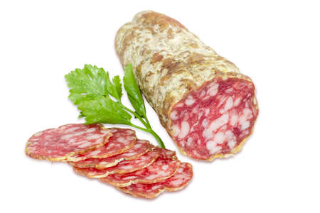 italian salami: Italian salami, some sliced thin slices of salami and sprig of parsley  on a light background