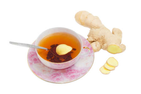 ginger tea: Cup of ginger tea with tea spoon on pink saucer and slices of a ginger against the backdrop of ginger root on a light background