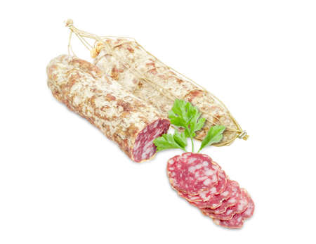 italian salami: Two italian salami, one of which is partially sliced thin slices and sprig of parsley  on a light background Stock Photo
