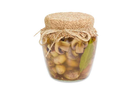 button mushroom: Pickled button mushrooms in glass jar on a light background