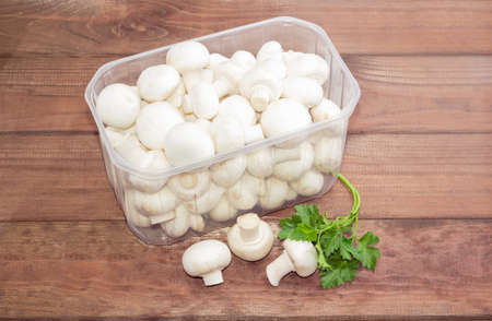button mushroom: Fresh uncooked button mushrooms in a transparent plastic tray, several mushrooms separately and a sprig of parsley on a dark wooden surface Stock Photo