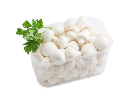 button mushroom: Fresh uncooked button mushrooms in a transparent plastic tray and a sprig of parsley on a light background