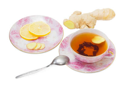 tea spoon: Cup of ginger tea on pink saucer, a tea spoon and saucer with slices of a ginger and lemon against the backdrop of ginger root on a light background