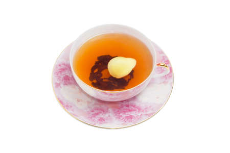 ginger tea: Cup of ginger tea with slice of a fresh ginger on pink saucer on a light background