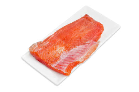 Piece of fresh uncooked fillet of rainbow trout on a rectangular white plate on a light background