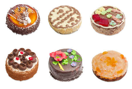 differently: Several various round sponge cake decorated differently - with slices jelly, chocolate and chocolate glazing, whipped cream and cream with cocoa powder and floral pattern made from cream on a light background Stock Photo