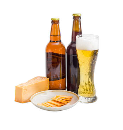 beerhouse: Beer glass with lager beer, two various bottles beer, one piece and several thin slices of hard cheese on saucer on a light background