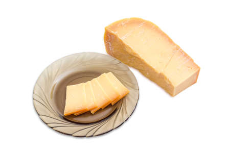 Piece of Dutch cheese Beemster and several thin slices of the same cheese on dark glass saucer on a light background 스톡 콘텐츠