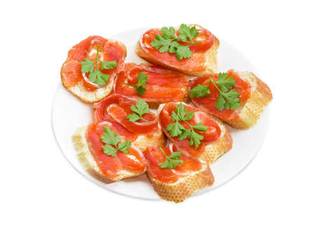 rainbow trout: Sandwiches made with pieces of baguette, butter, slices of a salted rainbow trout and parsley leaves on white dish on a light background