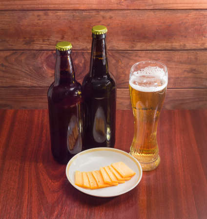 hard cheese: Glass of lager beer, two bottles beer and several thin slices of hard cheese on saucer on wooden table against the backdrop of dark wooden planks Stock Photo